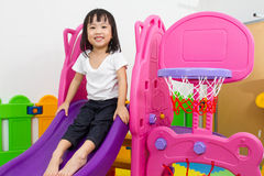 Asian Chinese little girl playing on the slide. At indoor colourful playground Royalty Free Stock Images
