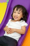 Asian Chinese little girl playing on the slide. At indoor colourful playground Royalty Free Stock Image