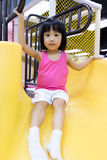 Asian Chinese Little Girl Playing on the Slide. At Indoor Colourful Playground Royalty Free Stock Photo