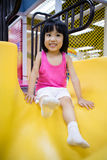 Asian Chinese Little Girl Playing on the Slide. At Indoor Colourful Playground Stock Images