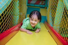 Asian Chinese little girl playing slide. At indoor playground alone Stock Image
