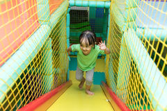 Asian Chinese little girl playing slide. At indoor playground alone Stock Images