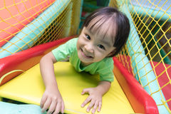 Asian Chinese little girl playing slide. At indoor playground alone Royalty Free Stock Image