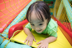 Asian Chinese little girl playing slide. At indoor playground alone Royalty Free Stock Photography