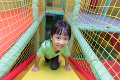 Asian Chinese little girl playing slide. At indoor playground alone Royalty Free Stock Images