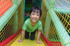 Asian Chinese little girl playing slide. At indoor playground alone Stock Photography