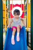 Asian Chinese little girl playing on the slide. At outdoor playground Royalty Free Stock Image