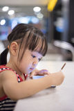 Asian Chinese little girl playing smartphone Royalty Free Stock Image