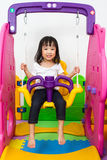 Asian Chinese little girl playing on swing Stock Photo