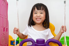 Asian Chinese little girl playing on swing Stock Photography