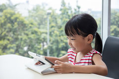 Asian Chinese little girl playing tablet computer Royalty Free Stock Photography