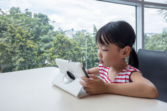 Asian Chinese little girl playing tablet computer Royalty Free Stock Photo