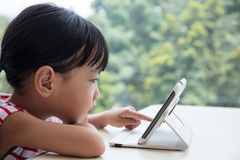 Asian Chinese little girl playing tablet computer Stock Photo