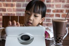 Asian Chinese little girl playing tablet computer. At indoor cafe Royalty Free Stock Photography