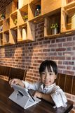 Asian Chinese little girl playing tablet computer. At indoor cafe Royalty Free Stock Images