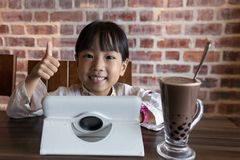 Asian Chinese little girl playing tablet computer. At indoor cafe Royalty Free Stock Photos