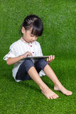 Asian Chinese little girl playing with tablet computer Stock Images