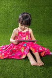Asian Chinese little girl playing tablet computer Royalty Free Stock Image