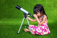 Asian Chinese little girl playing with a telescope Royalty Free Stock Photos