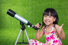 Asian Chinese little girl playing with a telescope Royalty Free Stock Images