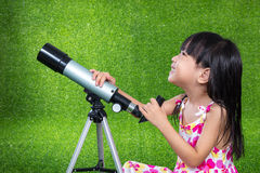Asian Chinese little girl playing with a telescope Stock Image