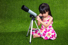 Asian Chinese little girl playing with a telescope Stock Images