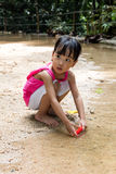 Asian Chinese little girl playing toy boat at creek Royalty Free Stock Photos