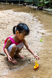 Asian Chinese little girl playing toy boat at creek Stock Photos