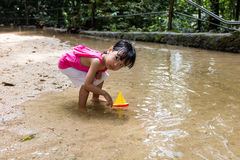 Asian Chinese little girl playing toy boat at creek Stock Images