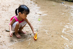 Asian Chinese little girl playing toy boat at creek Royalty Free Stock Photo