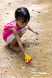Asian Chinese little girl playing toy boat at creek Royalty Free Stock Images