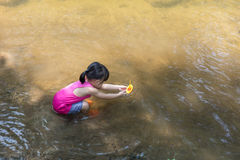 Asian Chinese little girl playing toy boat in the creek Stock Images