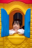 Asian Chinese little girl playing in toy house. At indoor playground Royalty Free Stock Images