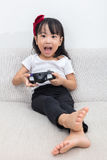 Asian Chinese little girl playing TV games on the sofa Royalty Free Stock Photos