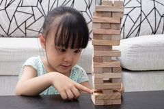 Asian Chinese little girl playing wooden stacks. At home Royalty Free Stock Image