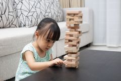 Asian Chinese little girl playing wooden stacks. At home Stock Photos