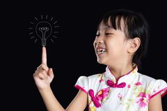 Asian chinese little girl pointing finger up to bulb royalty free stock images