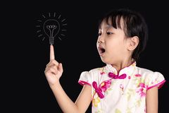 Asian chinese little girl pointing finger up to bulb stock photography
