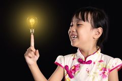 Asian chinese little girl pointing finger up to light bulb stock images