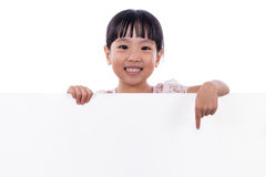 Asian Chinese little girl pointing at white board Stock Photography