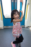 Asian Chinese little girl pole dancing inside a MRT transit Stock Photos