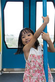 Asian Chinese little girl pole dancing inside a MRT transit Stock Images