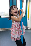 Asian Chinese little girl pole dancing inside a MRT transit Royalty Free Stock Photo
