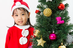 Asian Chinese little girl posing with Christmas Tree Stock Images