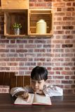 Asian Chinese little girl reading book. At home Stock Photo
