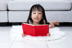 Asian Chinese little girl reading book on the floor Royalty Free Stock Photo