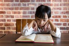 Asian Chinese little girl reading book. At home Stock Image