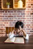 Asian Chinese little girl reading book. At home Stock Photos