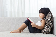 Asian Chinese little girl reading book on the sofa. Asian Chinese little girl lying down on the sofa reading book in the living room at home Stock Photo
