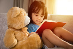 Asian Chinese little girl reading book with teddy bear stock photos